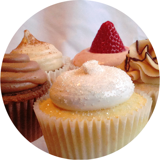 shown here are several delicious flavors: vanilla with italian merengue, milk chocolate with milk chocolate buttercream, strawberry with strawberry cream cheese, banana with peanut butter buttercream, and nice spice with cream cheese icing.
